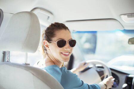 transportation: Portrait of confident woman in sunglasses driving car LANG_EVOIMAGES