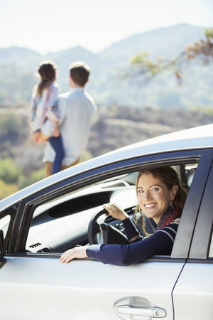 Portrait of smiling woman inside of car