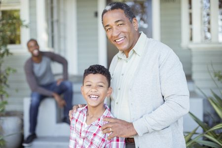 Portrait of smiling grandfather and grandson outside house