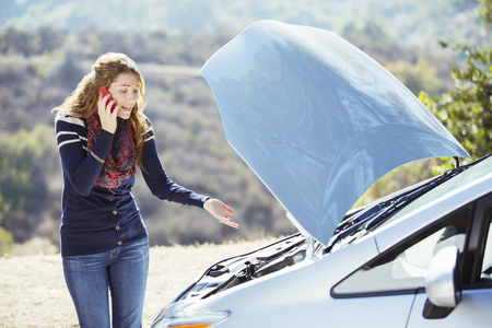 Frustrated woman talking on cell phone with automobile hood raised at roadside LANG_EVOIMAGES