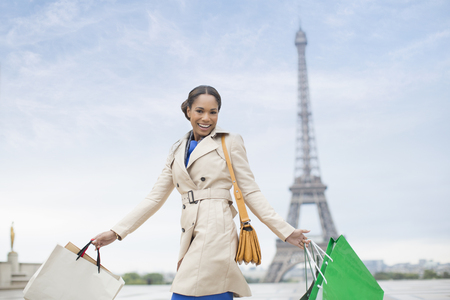 retail scene: Woman carrying shopping bags by Eiffel Tower, Paris, France