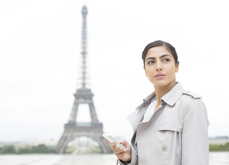 Businesswoman using cell phone near Eiffel Tower, Paris, France