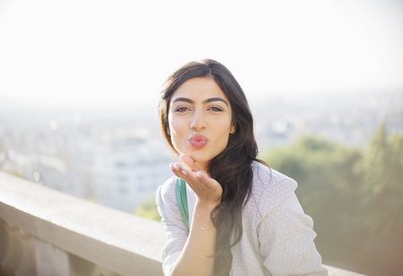 Woman blowing a kiss outdoors