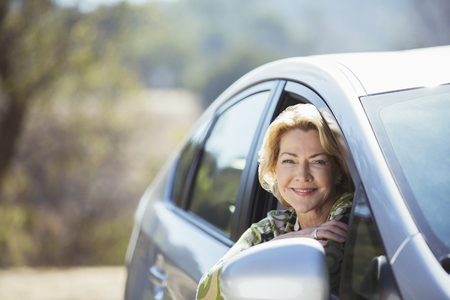 looking away from camera: Portrait of confident senior woman leaning out car window