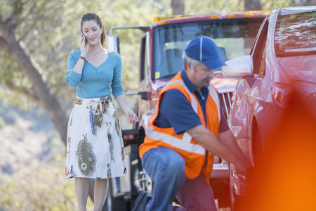 Roadside mechanic fixing flat tire for woman on cell phone