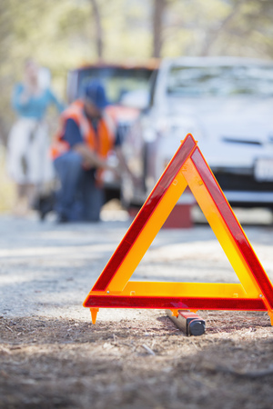 inconvenience: Roadside mechanic helping woman behind warning triangle LANG_EVOIMAGES