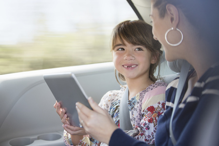 Happy mother and daughter using digital tablet in back seat of car