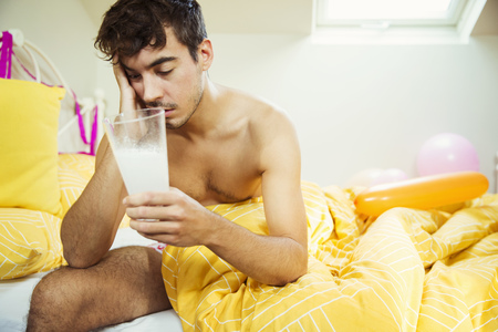 Hungover man drinking concoction in bed the morning after a party