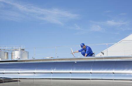 arrodillarse: Trabajador en plataforma sobre cisterna de leche de acero inoxidable. LANG_EVOIMAGES