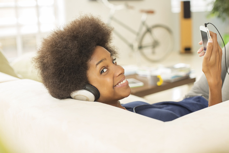 mp3 player: Woman listening to headphones on sofa LANG_EVOIMAGES