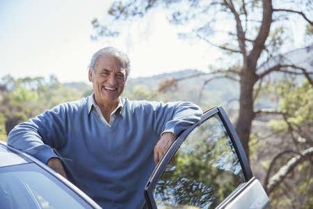 transportation: Portrait of happy senior man leaning on car