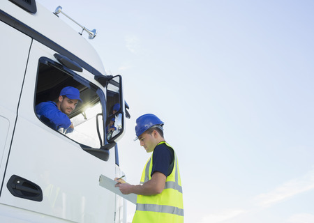 truck driver: Worker with clipboard talking to truck driver LANG_EVOIMAGES