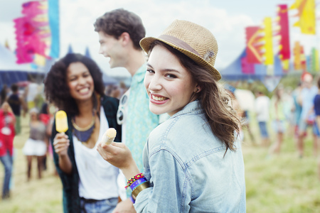 smile close up: Portrait of woman eating flavored ice with friends at music festival