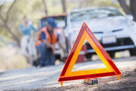 arrodillarse: Triángulo de advertencia en carretera con mecánico en segundo plano
