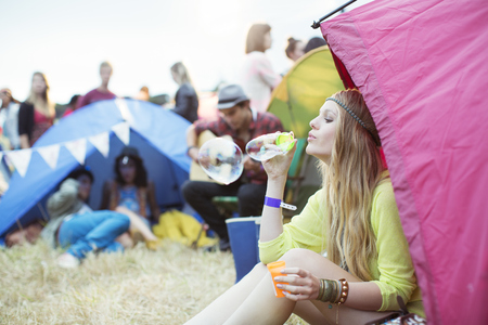 Woman blowing bubbles from tent at music festival
