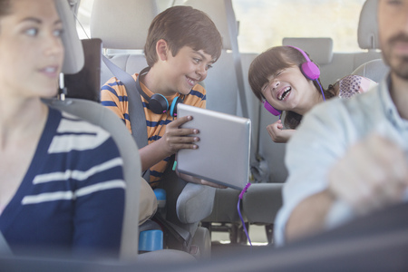 Happy brother and sister using digital tablet in back seat of car LANG_EVOIMAGES
