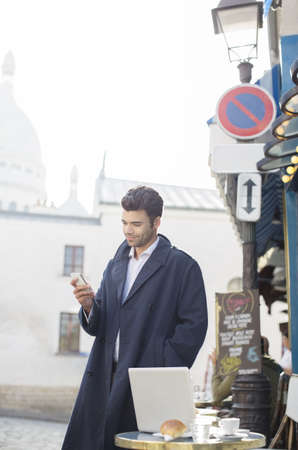 french ethnicity: Businessman using cell phone at sidewalk cafe