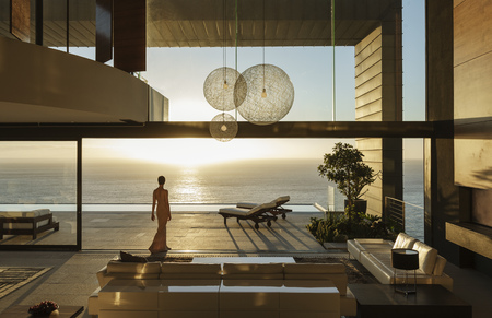 Woman in modern house overlooking ocean