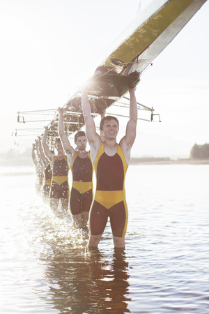 Rowing team carrying scull overhead in lake