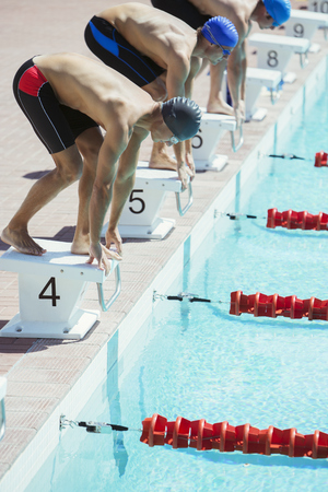 poised: Swimmers poised at starting blocks