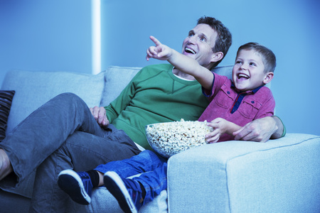 high definition television: Father and son watching television in living room LANG_EVOIMAGES