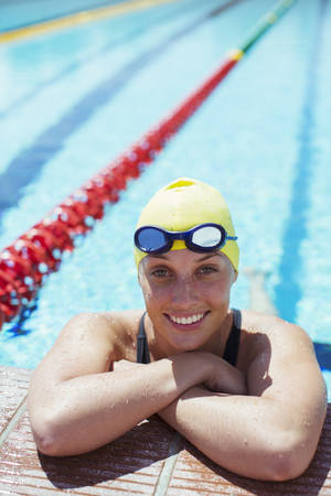 Portrait of smiling swimmer leaning at edge of pool