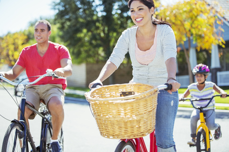 transportation: Happy family riding bikes on sunny street LANG_EVOIMAGES