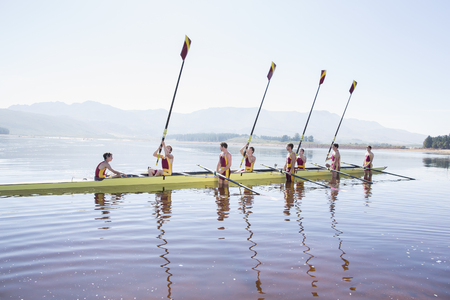 Rowing team with oars raised on lake LANG_EVOIMAGES