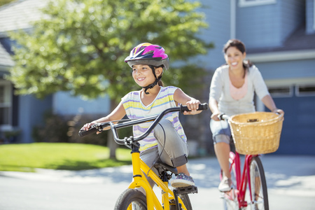 transportation: Mother and daughter riding bicycles in sunny street