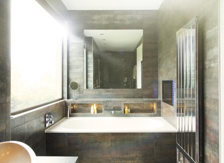 bathroom mirror: Bathtub and mirror in modern bathroom LANG_EVOIMAGES