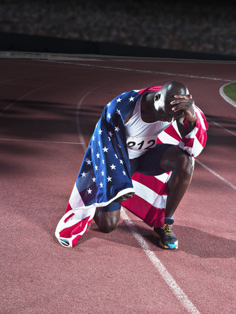 humility: Track and field athlete wrapped in American flag on track