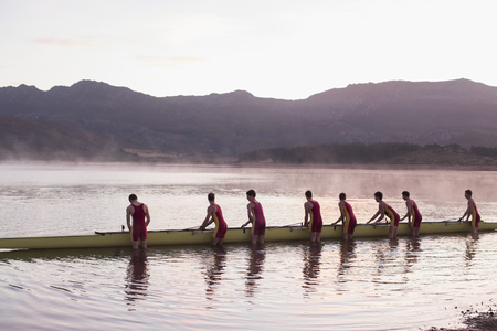 Rowing crew placing scull in lake at dawn