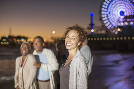 looking away from camera: Portrait of confident woman on beach with friends at night