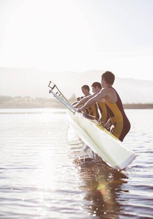Rowing team placing boat in lake