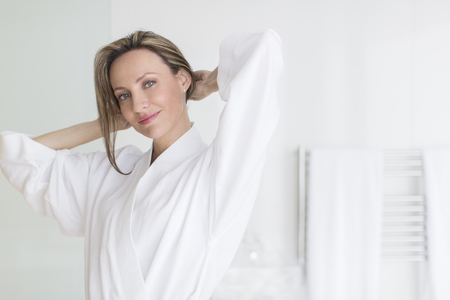 arms behind head: Smiling woman wearing bathrobe LANG_EVOIMAGES