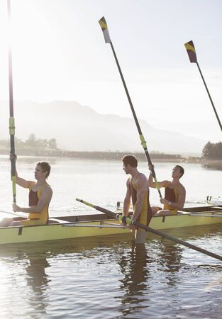 Rowing team lifting oars in lake LANG_EVOIMAGES