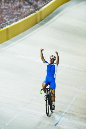 velodrome: Track cyclist celebrating in velodrome