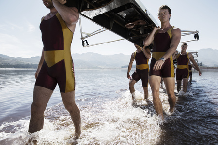 Rowing team carrying scull out of lake