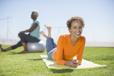 Portrait of smiling woman on yoga mat in park LANG_EVOIMAGES