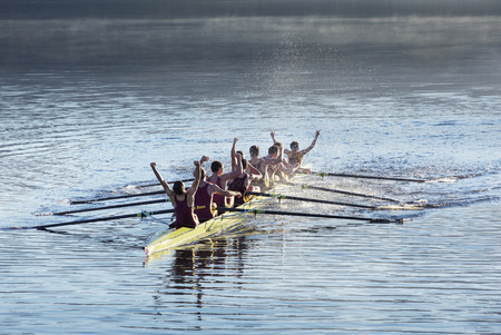 Rowing team celebrating in scull on lake