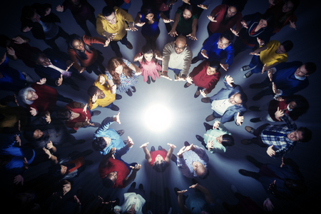 looking away from camera: Business people forming circle around bright light LANG_EVOIMAGES
