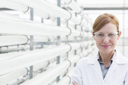 smile close up: Portrait of confident scientist next to irrigation pipes in greenhouse