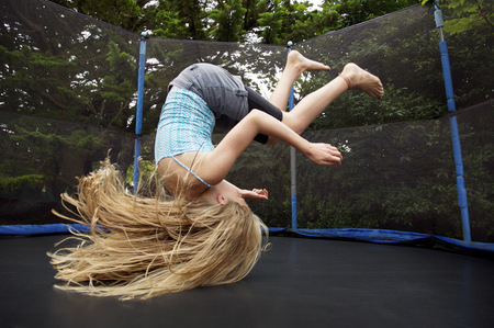 bounding: Girl jumping on trampoline outdoors