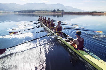 Rowing team rowing scull on lake LANG_EVOIMAGES