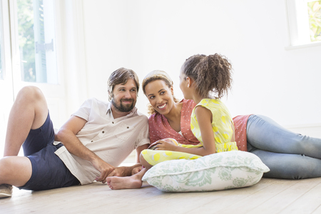 sitting on the ground: Family sitting on the ground in living space