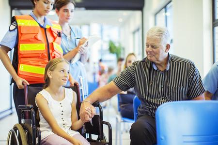 Man holding granddaughter's hand in hospital
