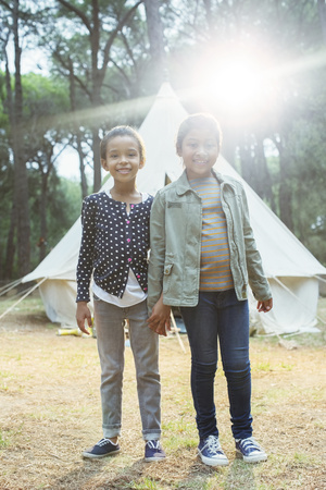 Girls smiling by teepee at campsite