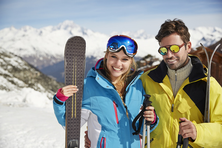 looking away from camera: Couple carrying skis on mountain top