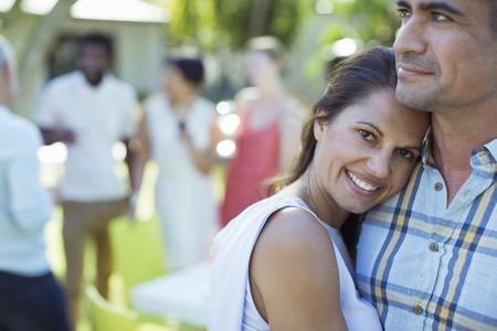 socializando: Couple hugging at dinner party