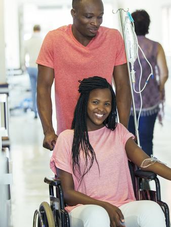 Man wheeling girlfriend in hospital hallway